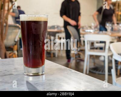 Dunkles Bier, das auf dem Tisch im Restaurant sitzt, und die Gäste sitzen