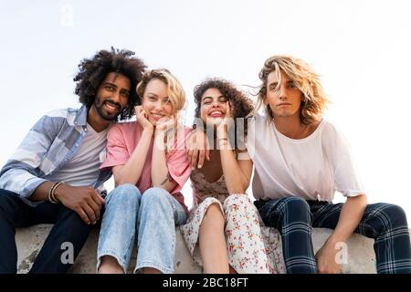 Porträt von glücklichen Freunden sitzen an einer Wand im Freien