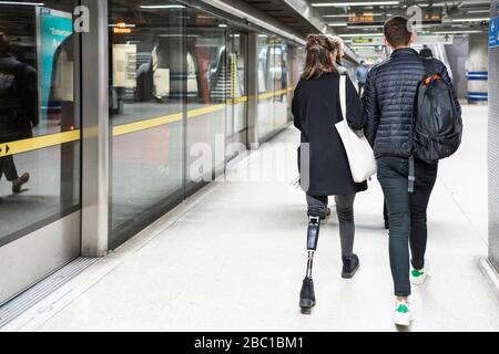 Rückansicht der jungen Frau mit Beinprothese und Mann zu Fuß an der U-Bahn-Station platfom - Stockfoto