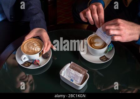 Ein Paar, das den Service und die Aufmerksamkeit mit zwei Tassen Kaffee genießt - Stockfoto