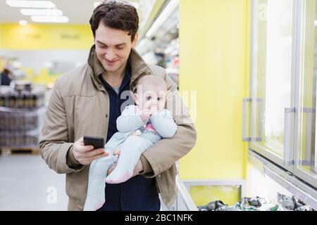 Vater mit Tochter überprüft Smartphone, kauft im Supermarkt ein - Stockfoto