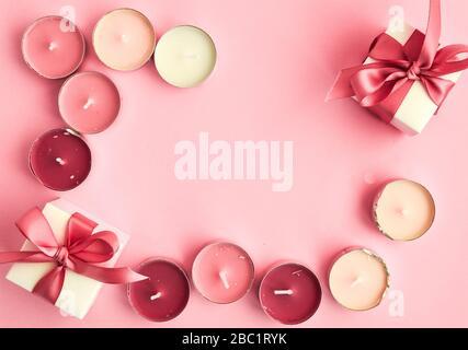 Geschenkschachteln mit rosafarbenem Band und Kerzen auf rosafarbenem Hintergrund und Platz für Text Stockfoto