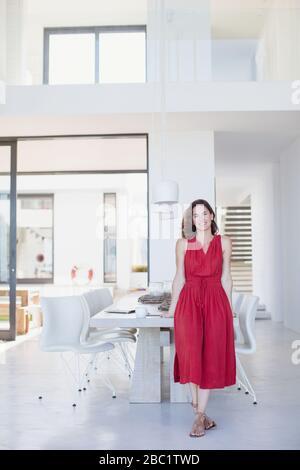 Portrait lächelnde brünette Frau in rotem Kleid auf Esstisch gelehnt - Stockfoto