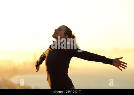 Fröhlicher Läufer, der frische Luft atmet, die sich bei Sonnenuntergang in den Randgebieten der Stadt ausdehnt