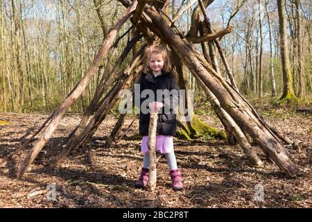 Kind / Kinder / Junges Mädchen und ein Wigwam Baumstapel Äste, die sich auf einem Baum niedergelehnt haben – Forest School – ein Frühlingstag in Waldwäldern am West End Common, Esher in Surrey, Großbritannien (116) - Stockfoto