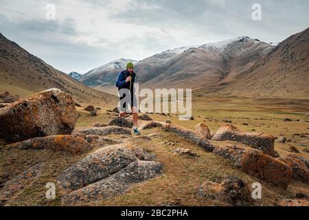 Männlicher Läufer, der auf einem Bergweg läuft. Der Athlet läuft in den Bergen unter den Felsen. Mann trainiert im Freien. Trail Running