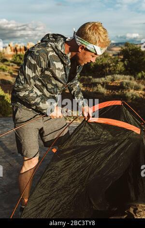 Männlicher Wanderer in Camo-Jacke und Kopfbank stellt Zelt in der Wüste auf - Stockfoto