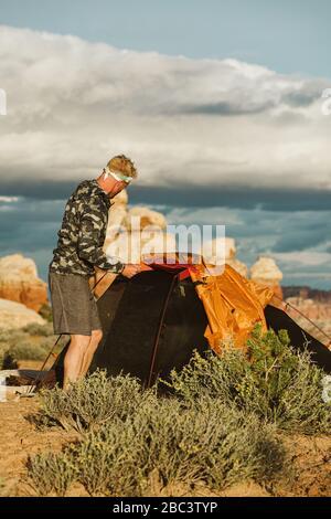 Mann in Camo-Jacke stellt Zelt bei Sonnenuntergang in der Wüste von utah auf - Stockfoto
