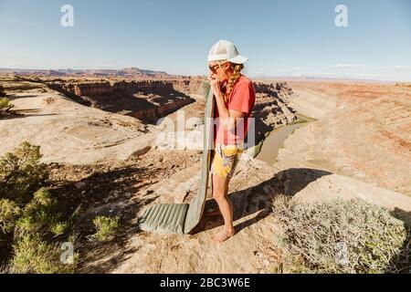 Camper bläst Schlafpolster auf einem Campingplatz über dem Grand Canyon auf - Stockfoto