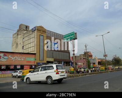 Agra, Uttar Pradesh, Indien - März 2018: Straßenansicht mit Gebäuden und Autos auf der Straße in Agra. - Stockfoto