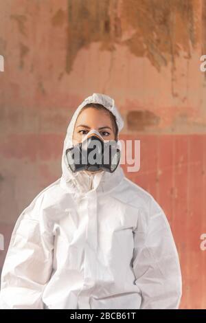 Junge Virologe Ärztin mit einem weißen Biohazard Schutzanzug und Gesichtsmaske während der Grippe Corona Virus Ausbruch Pandemie - Stockfoto