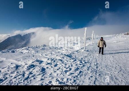 Mann in seinen sechziger Jahren Wandern im Winter am Polnisch-tschechischen Freundschaftsweg, entlang der polnischen und tschechischen Grenze, Föhn Wolke, subalpine Hochebene über tim - Stockfoto