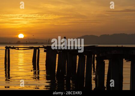 Schöner Sonnenaufgang über dem Meer in der Nähe der Holzbrücke am Fischersteg Penang, Malaysia. - Stockfoto