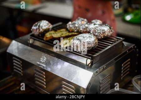 Kartoffeln in Aluminiumfolie, Grillen auf bbq, Sommeressen. - Stockfoto
