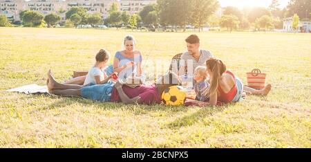 Glückliche Familien, die im Stadtpark Picknick machen - junge Eltern haben Spaß mit ihren Kindern im Sommer zusammen essen, trinken und lachen - Love a - Stockfoto