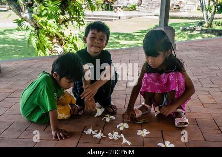 Balinesische Kinder, die mit magnolia Flowers spielen - Stockfoto