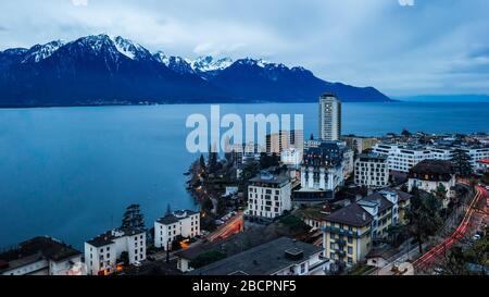 Ein Blick auf Lausanne und die Alpen in der Schweiz in der Abenddämmerung. - Stockfoto