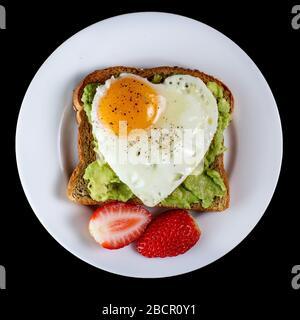 Toast mit Avocado und Ei mit Herzform auf weißem Teller isoliert auf schwarzem Hintergrund - Stockfoto