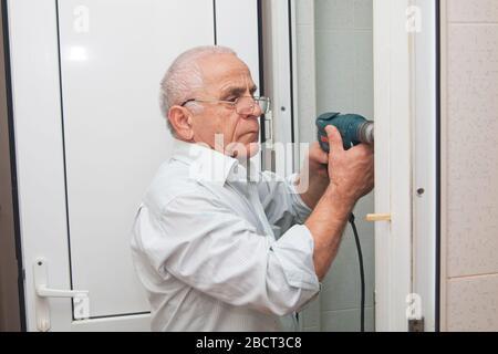 Der Mann installiert den Türgriff mit einem Bohrer. Reparaturarbeiten. Wartung in der Wohnung. Mann bohrt ein Loch in einer Tür . Mann bohrt ein Loch in A. - Stockfoto