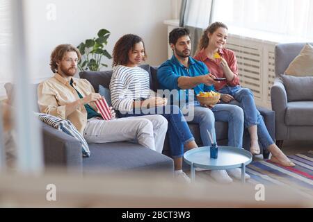 Porträt einer Gruppe von Freunden aus verschiedenen ethnischen Gruppen, die gemeinsam Fernsehen, während sie zu Hause auf einem bequemen Sofa sitzen und Snacks essen, Platz für Kopien - Stockfoto