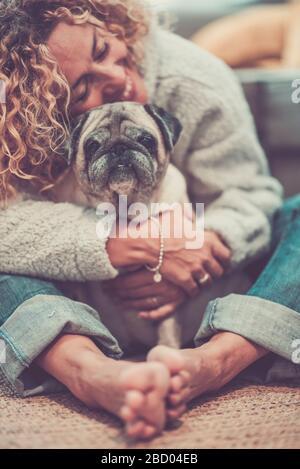 Liebe und Freundschaftskonzept mit einer glücklichen, entschärften kaukasischen erwachsenen Frau umarmen ihren lieblichen alten Hundepug - Tiertherapie und beste Freundin für immer zusammen - Stockfoto