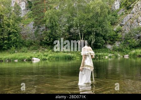 Rückansicht Porträt der jungen schönen dunkelhaarigen Dame im langen weißen Kleid, das knöcheltief im Waldfluss steht und etwas im Wasser sucht. Romanti Stockfoto