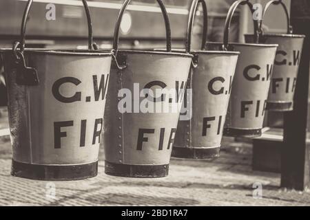 Schwarz-weiße Nahaufnahme, alte Feuereimer, die in einer vierreihigen Reihe auf dem Bahnsteig des alten Dampfbahnhofs Severn Valley Railway Line aufhängen. - Stockfoto