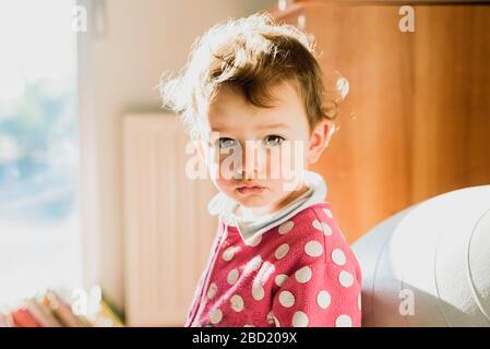 Portrait von liebenswürdig geborenem Mädchen mit Hintergrundbeleuchtung ein warmer Morgen in seiner Entwicklung. - Stockfoto