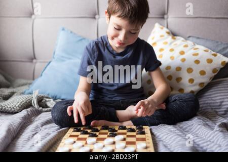 Junge Kinder spielen mit den Schachspielen ein Tischspiel im Bett. Bleiben Sie zu Hause Quarantänekonzept. Freizeitkonzept für Brettspiele und Kinder. Familienzeit.