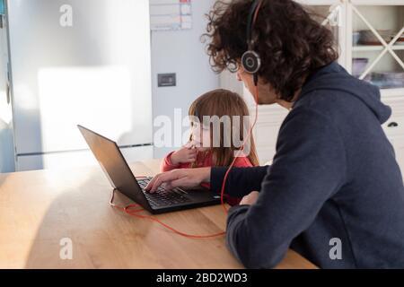 Junger Vater, der während der kovid-19-Sperre von zu Hause aus mit kleiner Tochter arbeitet. Kinder, die während der sozialen Isolation auf den Laptop von Papa blicken - Stockfoto