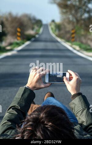 Frau liegt auf dem Boden, Straße mit Handy in den Händen - Stockfoto