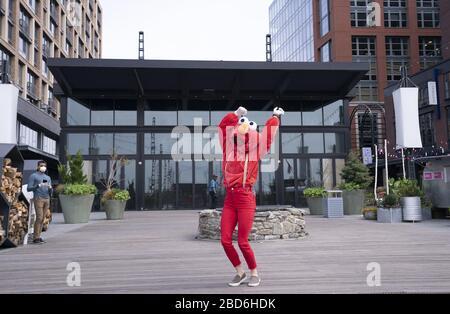 """Washington DC, USA. April 2020. Ein YouTube-Darsteller, bekannt als """"Elmo at the Wharf"""", tanzt am Wharf in Washington, DC während der Pandemie von Coronavirus und bleibt am Dienstag, den 7. April 2020 zu Hause. Die Darstellerin sagte, sie habe versucht, den Menschen in den Apartmentgebäuden, die den Bereich überblicken, Lächeln und Freude zu bringen. Foto von Kevin Dietsch/UPI Credit: UPI/Alamy Live News - Stockfoto"""