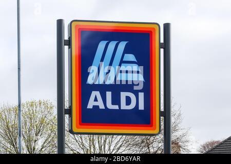 Aldi-Firmenschild mit Logo auf erhöhten Pols außerhalb eines Ladengeländes, Kilmarnock, Großbritannien - Stockfoto