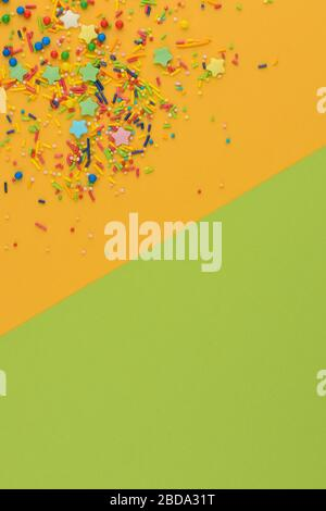 Dekorative Einsprengungen umrahmen auf gelbem und grünem Hintergrund. Farbblöcke. Mehrfarbiges Zuckerpulver in der Ecke. Verstreuter süßer Zucker - Stockfoto