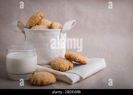 Hausgemachte Kekse in einem Leinenkorb auf beigefarbenem Hintergrund. Geknickte Plätzchen