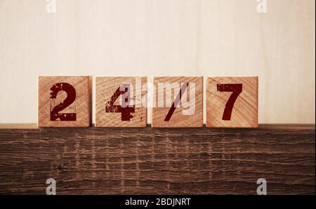 Text rund um die Uhr auf Würfeln auf Holzhintergrund. Kundenkonzept unterstützen Stockfoto