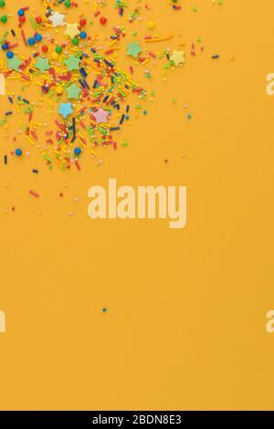 Dekorative Einsprengungen umranden auf gelbem Hintergrund. Mehrfarbiges Zuckerpulver in der Ecke. Verstreute süße Zuckerstöcke, Sterne und Bälle - Stockfoto
