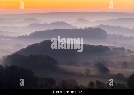 Bridport, Dorset, Großbritannien. April 2020. Wetter in Großbritannien. Nebel in den Tälern umgibt die Hügel von Bridport in Dorset bei Sonnenaufgang vor einem weiteren warmen sonnigen Frühlingstag. Bildnachweis: Graham Hunt/Alamy Live News - Stockfoto
