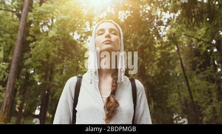Entspannte junge Frau, die in der Natur spazieren geht und sich entspannt fühlt, das Sonnenlicht scheint durch Bäume, das Entspannungskonzept und das Konzept der Achtsamkeit - Stockfoto