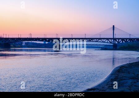 Warschauer Swietokrzyski-Brücke über den Fluss Wisla in der Dämmerung. - Stockfoto