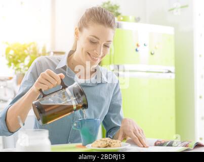 Junge Frau mit einer Tasse Tee und einem Snack: Sie ist entspannend, gießt Kaffee und das Lesen einer Zeitschrift - Stockfoto