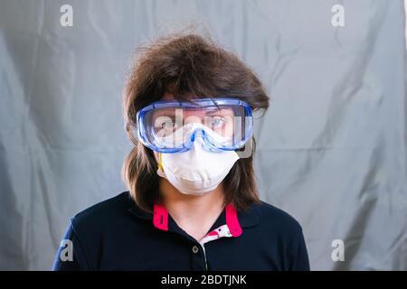 Junge Frau in Schutzmaske und blaue Schutzbrille während der Selbstisolierung und Quarantäne. Sie mag es nicht. Bleib zu Hause - Stockfoto