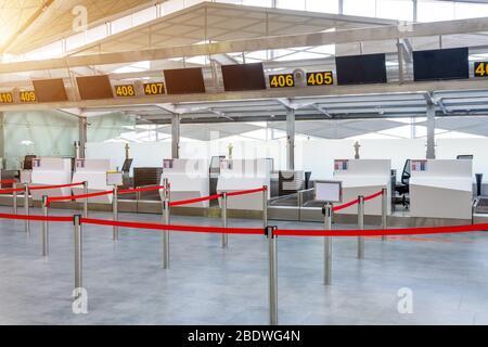 Leere Abfertigungsschalter für die Gepäckaufgabe, deren Pfade mit einem roten Band abgesagt wurden, um die Passagiere am Flughafenterminal zu unterscheiden - Stockfoto