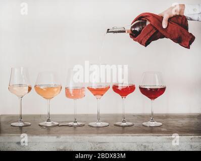 Roséweinschattierungen und Womans Hand Gießen Wein ins Glas - Stockfoto