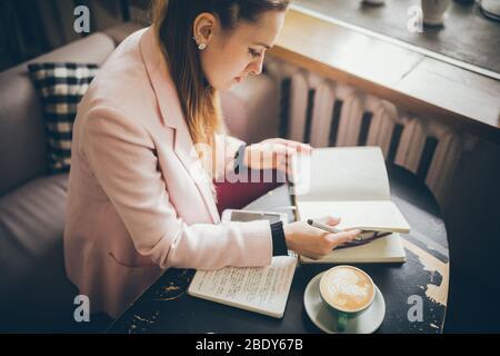 Arbeiten Sie bequem in einem Café. Freiberufliche Frau blättert durch die Seiten eines Tagebuchs in einem Café. Attraktive Frau, die im Restaurant Kaffee trinkt