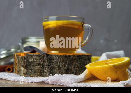 Gläserner durchsichtiger Becher mit Minztee steht auf einem Holzständer neben einer Zuckerschale mit Zuckerwürfeln, geschnittener Zitrone und einem Löffel - Stockfoto
