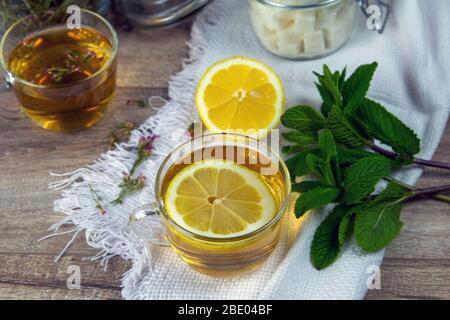 Gläserner durchsichtiger Becher mit Minztee steht auf einem Holzständer neben einer Zuckerschale mit Zuckerwürfeln, geschnittener Zitrone und Minzblättern - Stockfoto