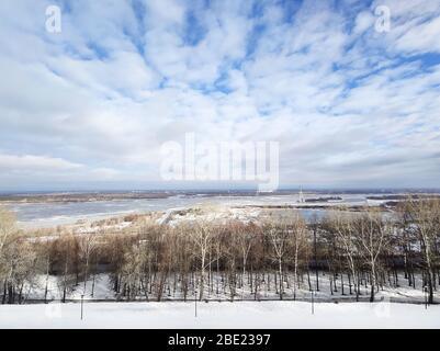 Schöne Flusslandschaft im frühen Frühling. Weiße Wolken über dem Fluss und Bäume an einem sonnigen Tag nach dem Schneeschmelzen.
