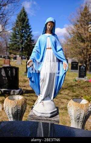 Kleine, farbenfrohe Statue der Jungfrau Maria (Pose der Madonna von Grace) auf einem Grabstein auf dem Beechwood Cemetery, Ottawa, Ontario, Kanada.