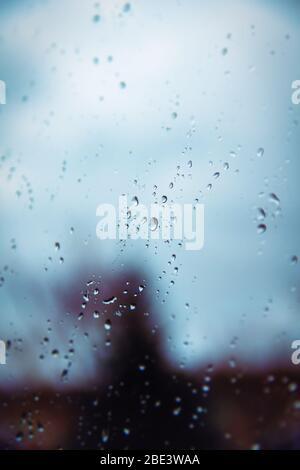 Selektiver Fokus von Regentropfen auf einer Glasfensteroberfläche mit verschwommenen Schatten und trüben Hintergrund. Dramatisches Hintergrundkonzept. - Stockfoto